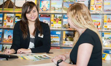 Een verkoper reizen adviseert een klant aan de balie van een reisbureau.