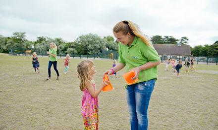 De leisure and hospitality host in de recreatie organiseert een activiteit voor kinderen op een camping.